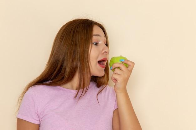 Vooraanzicht jonge aantrekkelijke vrouw in roze t-shirt en spijkerbroek appel bijten