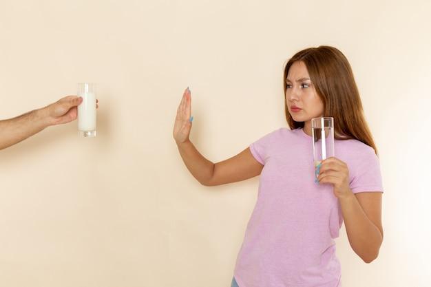 Vooraanzicht jonge aantrekkelijke vrouw in roze t-shirt en spijkerbroek glas water houden en melk weigeren