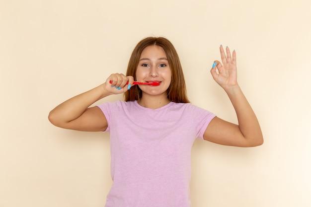Vooraanzicht jonge aantrekkelijke vrouw in roze t-shirt en spijkerbroek haar tanden met glimlach schoonmaken