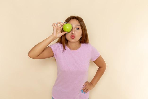 Vooraanzicht jonge aantrekkelijke vrouw in roze t-shirt en spijkerbroek met appel en poseren
