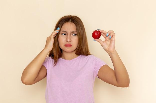 Vooraanzicht jonge aantrekkelijke vrouw in roze t-shirt en spijkerbroek met verse zure pruim