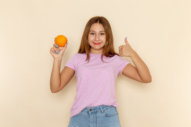 Vooraanzicht jonge aantrekkelijke vrouw in roze t-shirt en spijkerbroek oranje houden en ontzagwekkend teken tonen