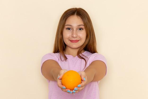 Vooraanzicht jonge aantrekkelijke vrouw in roze t-shirt en spijkerbroek oranje te houden en te geven