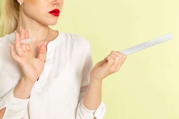 Vooraanzicht jonge aantrekkelijke vrouw in wit overhemd tot vaststelling van haar nagels op lichtgroene ondergrond