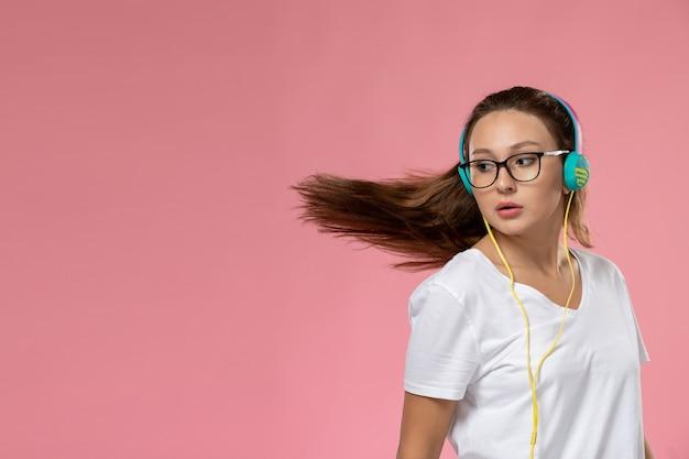 Vooraanzicht jonge aantrekkelijke vrouw in wit t-shirt gewoon poseren en luisteren naar muziek via oortelefoons met dansbewegingen op de roze achtergrond
