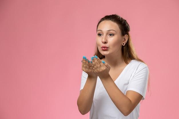 Vooraanzicht jonge aantrekkelijke vrouw in wit t-shirt lucht kussen verzenden op de roze achtergrond