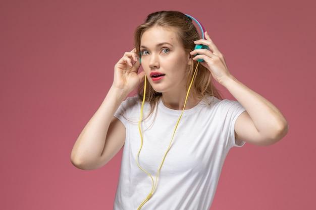 Vooraanzicht jonge aantrekkelijke vrouw in wit t-shirt luisteren naar muziek met koptelefoon op de roze muur model kleur vrouwelijke jong