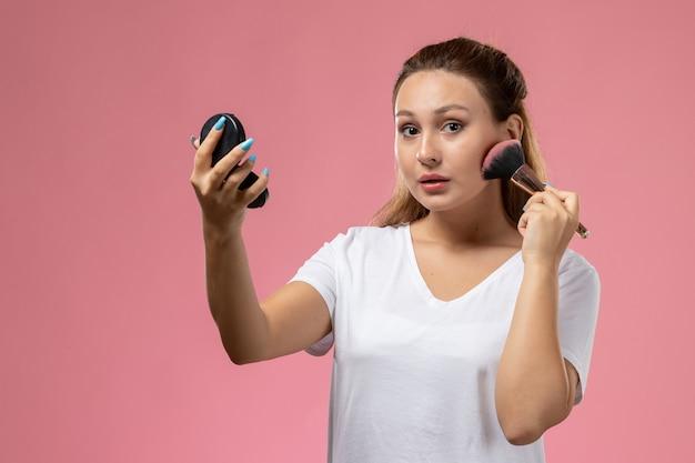 Vooraanzicht jonge aantrekkelijke vrouw in wit t-shirt make-up doen op zoek naar de camera op de roze achtergrond