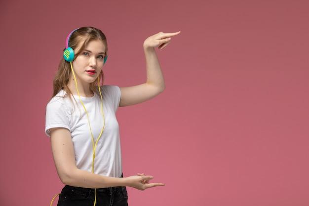 Vooraanzicht jonge aantrekkelijke vrouw in wit t-shirt met behulp van haar oortelefoons en het tonen van grootte met haar handen op donkerroze muur model kleur vrouwelijk jong meisje