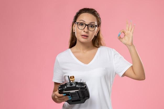 Vooraanzicht jonge aantrekkelijke vrouw in wit t-shirt poseren met afstandsbediening op de roze achtergrond