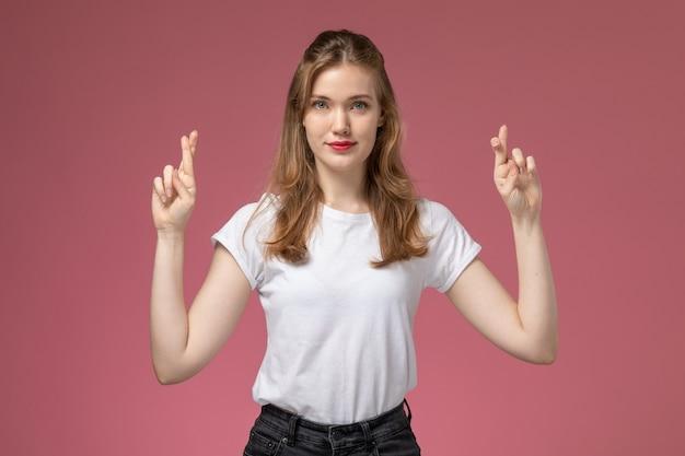 Vooraanzicht jonge aantrekkelijke vrouw in wit t-shirt poseren met gekruiste vingers en glimlach op de roze muur model vrouw pose kleurenfoto