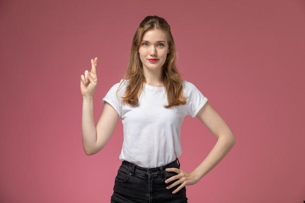 Vooraanzicht jonge aantrekkelijke vrouw in wit t-shirt poseren met gekruiste vingers op roze muur model vrouw pose kleurenfoto