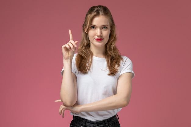 Vooraanzicht jonge aantrekkelijke vrouw in wit t-shirt poseren met opgetogen uitdrukking op roze muur model vrouwelijke pose kleur vrouwelijke jong