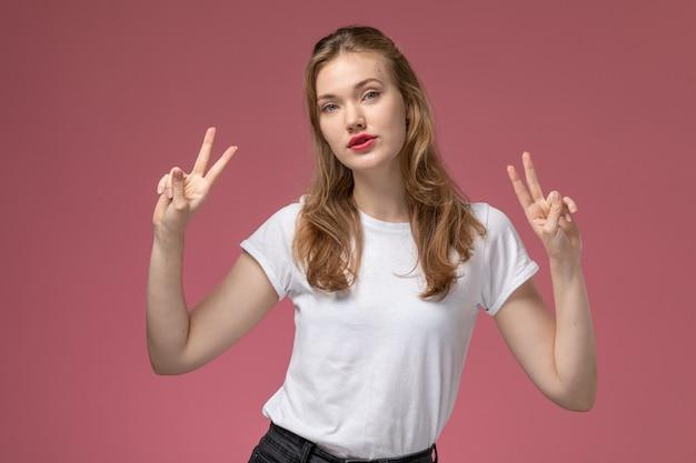 Vooraanzicht jonge aantrekkelijke vrouw in wit t-shirt poseren met overwinningsteken op roze muur model vrouwelijke pose kleurenfoto vrouwelijke jong
