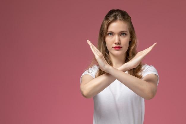 Vooraanzicht jonge aantrekkelijke vrouw in wit t-shirt poseren met verbodsteken op roze muur model vrouw pose kleurenfoto