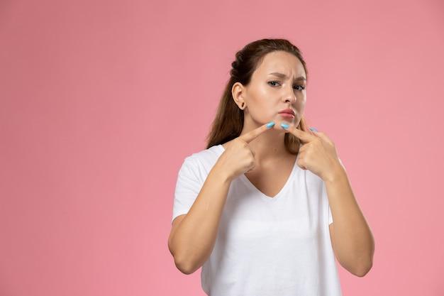 Vooraanzicht jonge aantrekkelijke vrouw in wit t-shirt wat betreft haar gezicht op de roze achtergrond