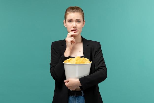Vooraanzicht jonge aantrekkelijke vrouwelijke bedrijf cips en kijken naar film op het lichtblauwe oppervlak