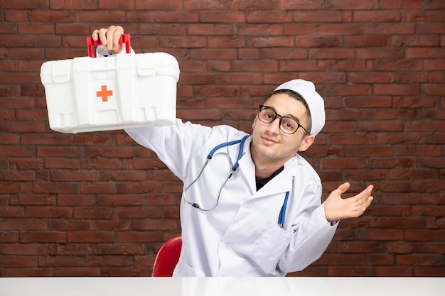 Vooraanzicht jonge arts in wit medisch pak met ehbo-kit