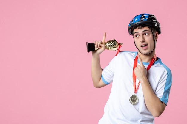 Vooraanzicht jonge atleet in sportkleding met gouden beker en medaille