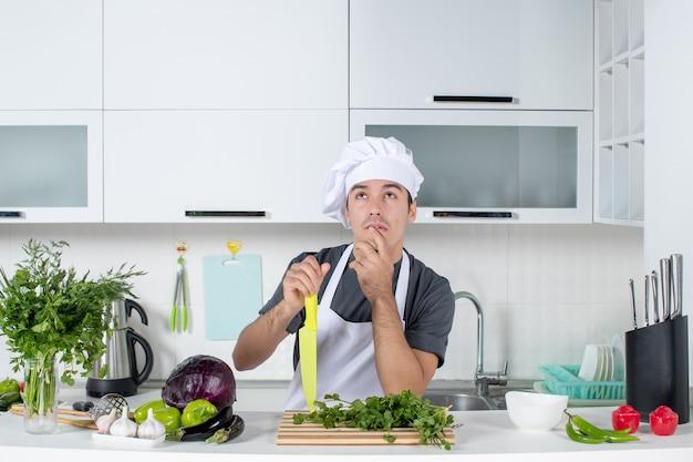 Vooraanzicht jonge chef-kok in uniform denken