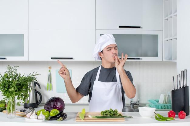 Vooraanzicht jonge chef-kok in uniform die chef-kok kust in de keuken