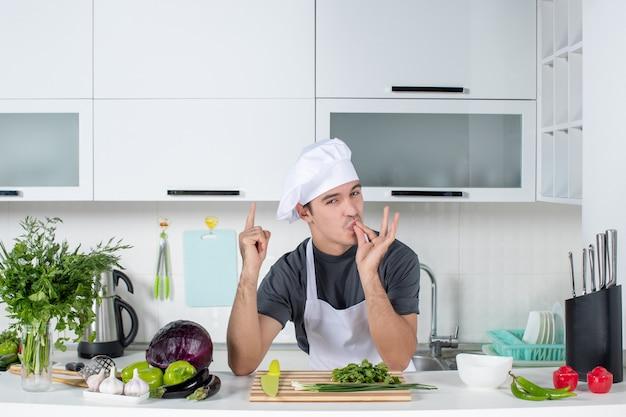 Vooraanzicht jonge chef-kok in uniform die chef-kok kusteken maakt