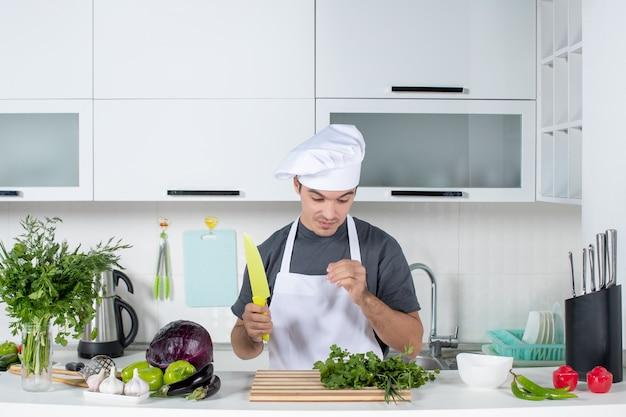 Vooraanzicht jonge chef-kok in uniform die naar zijn hand kijkt