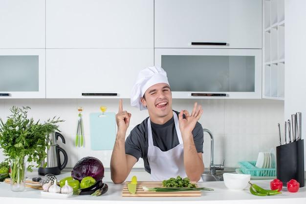 Vooraanzicht jonge chef-kok in uniform die okey teken maakt