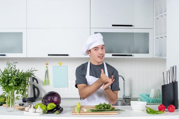 Vooraanzicht jonge chef-kok in uniform die speciaal handgebaar maakt
