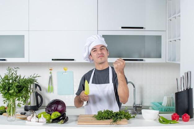 Vooraanzicht jonge chef-kok in uniform die zijn geluk toont