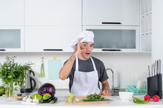Vooraanzicht jonge chef-kok in uniform die zijn oog wijd opent