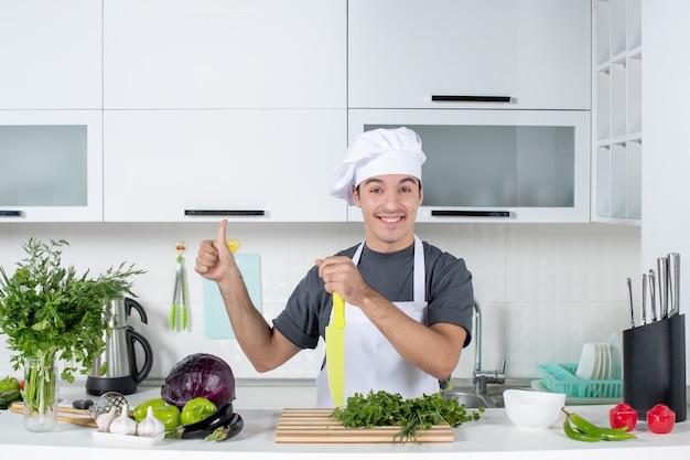 Vooraanzicht jonge chef-kok in uniform duimen omhoog maken