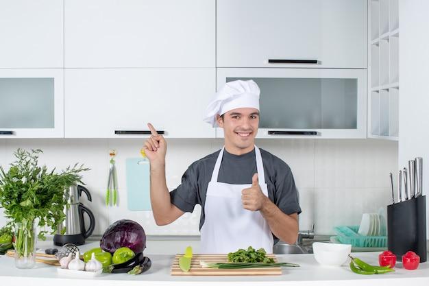 Vooraanzicht jonge chef-kok in uniform duimen omhoog teken maken