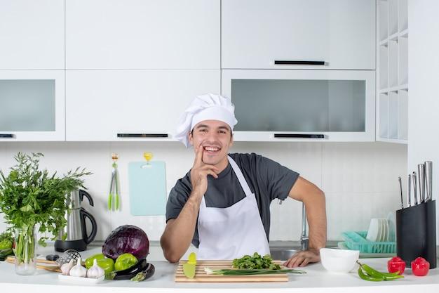 Vooraanzicht jonge chef-kok in uniform glimlachend