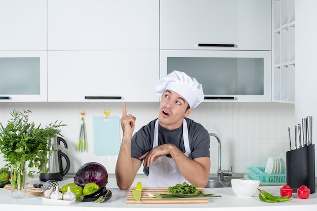 Vooraanzicht jonge chef-kok in uniform in keuken