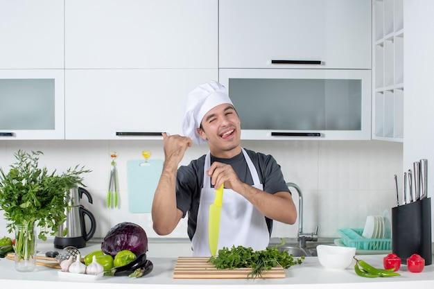 Vooraanzicht jonge chef-kok in uniform wijzend op kast