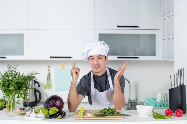 Vooraanzicht jonge chef-kok in uniform wijzende vinger omhoog