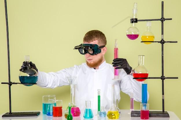 Vooraanzicht jonge chemicus creëren nieuwe chemische stof gemengd