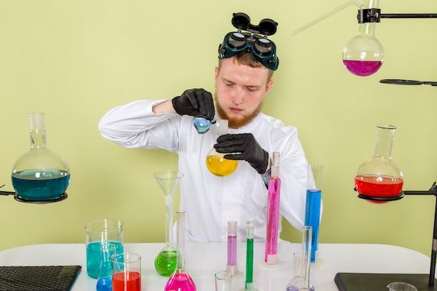 Vooraanzicht jonge chemicus die blauwe en gele chemicaliën mengt