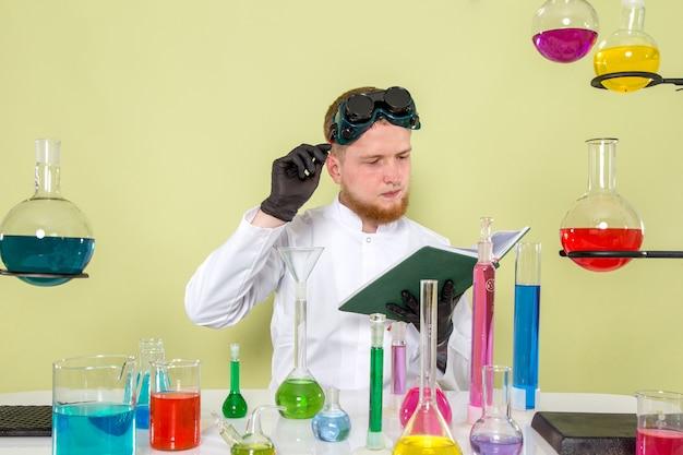 Vooraanzicht jonge chemicus die wat noodzakelijke informatie over chemicaliën leest