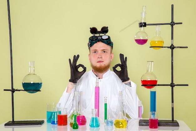 Vooraanzicht jonge chemicus houdt van zijn laatste chemische tests in een laboratorium
