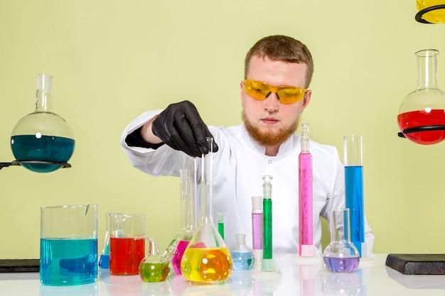 Vooraanzicht jonge chemicus met behulp van verschillende kolven in een laboratorium