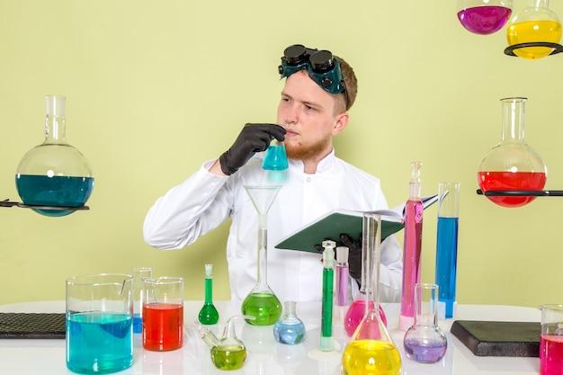 Vooraanzicht jonge chemicus onderscheidt chemicaliën met zijn neus
