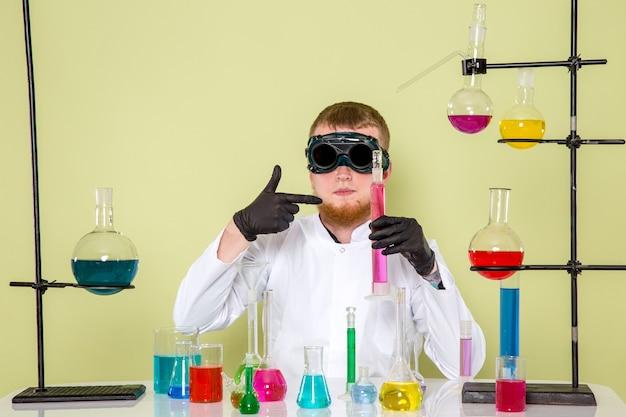 Vooraanzicht jonge chemicus toont zijn laatste gemengde chemicaliën