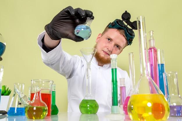 Vooraanzicht jonge chemicus wijst op zijn kleine kolf