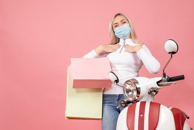Vooraanzicht jonge dame bedrijf boodschappentassen handen op haar borst in de buurt van bromfiets