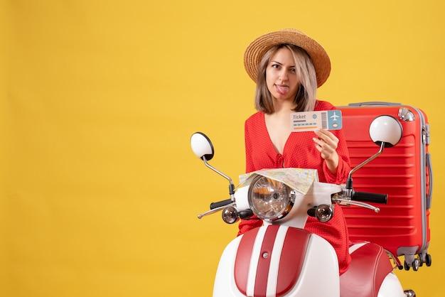 Vooraanzicht jonge dame die tong uitsteekt op bromfiets met rode koffer met ticket
