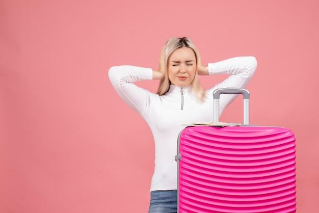 Vooraanzicht jonge dame die zich achter roze koffer bevindt die haar oren met handen sluit