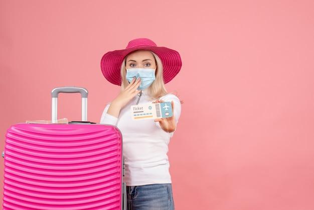 Vooraanzicht jonge dame die zich dichtbij het vliegticket van de kofferholding bevindt