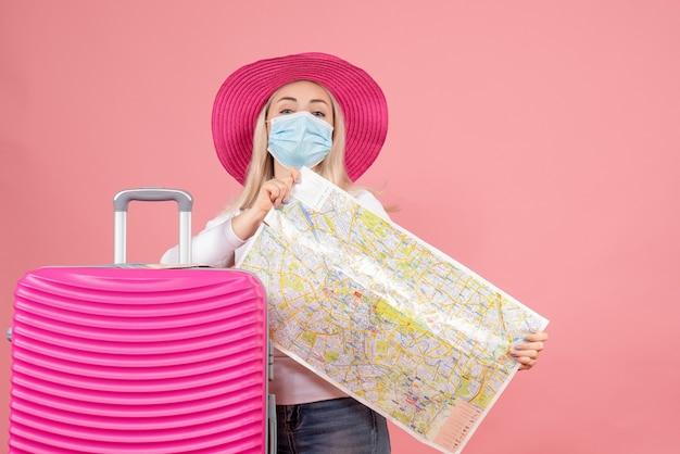 Vooraanzicht jonge dame in masker dat zich dichtbij de kaart van de kofferholding bevindt